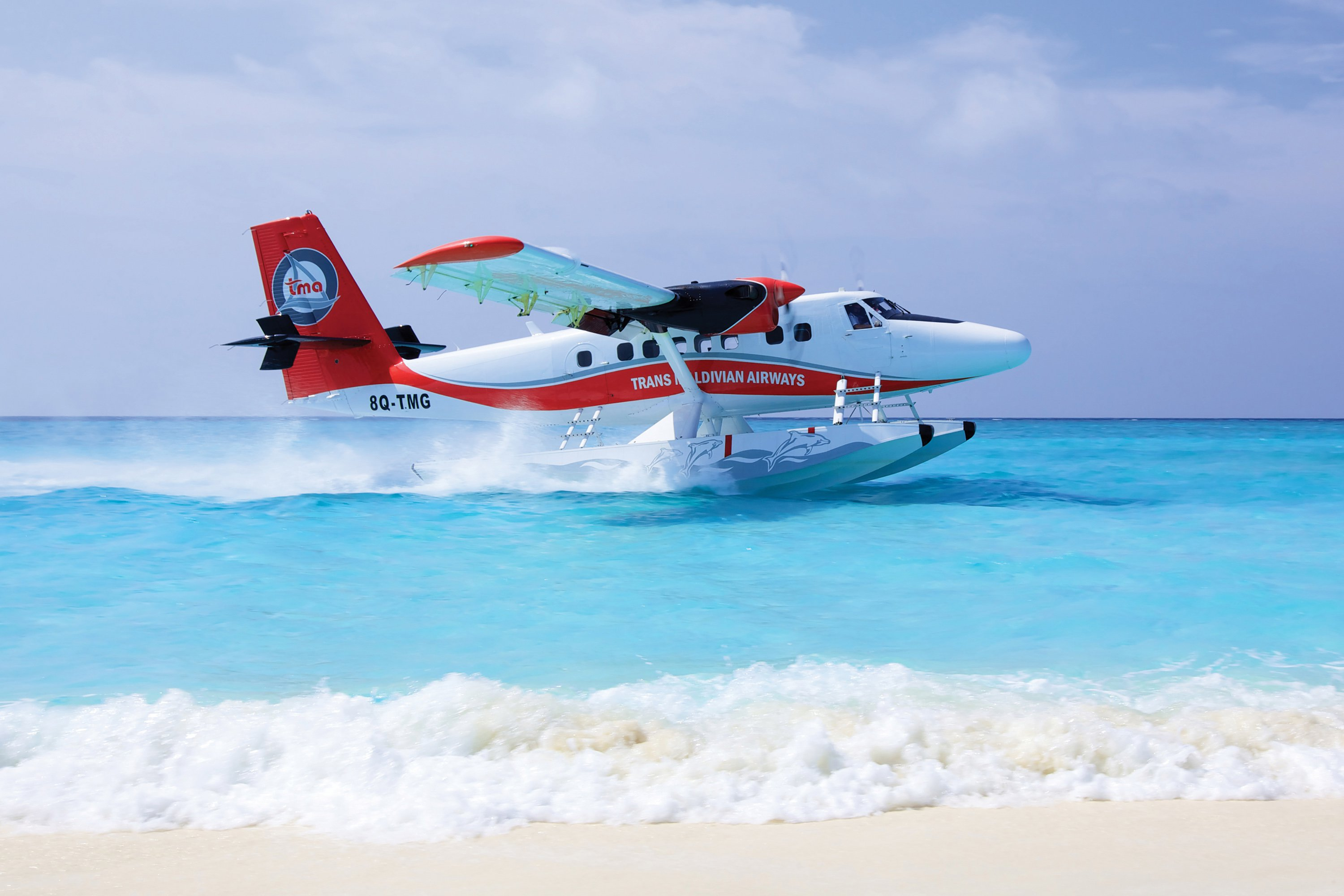 A picture of a floatplane landing on a blue ocean next to the beach