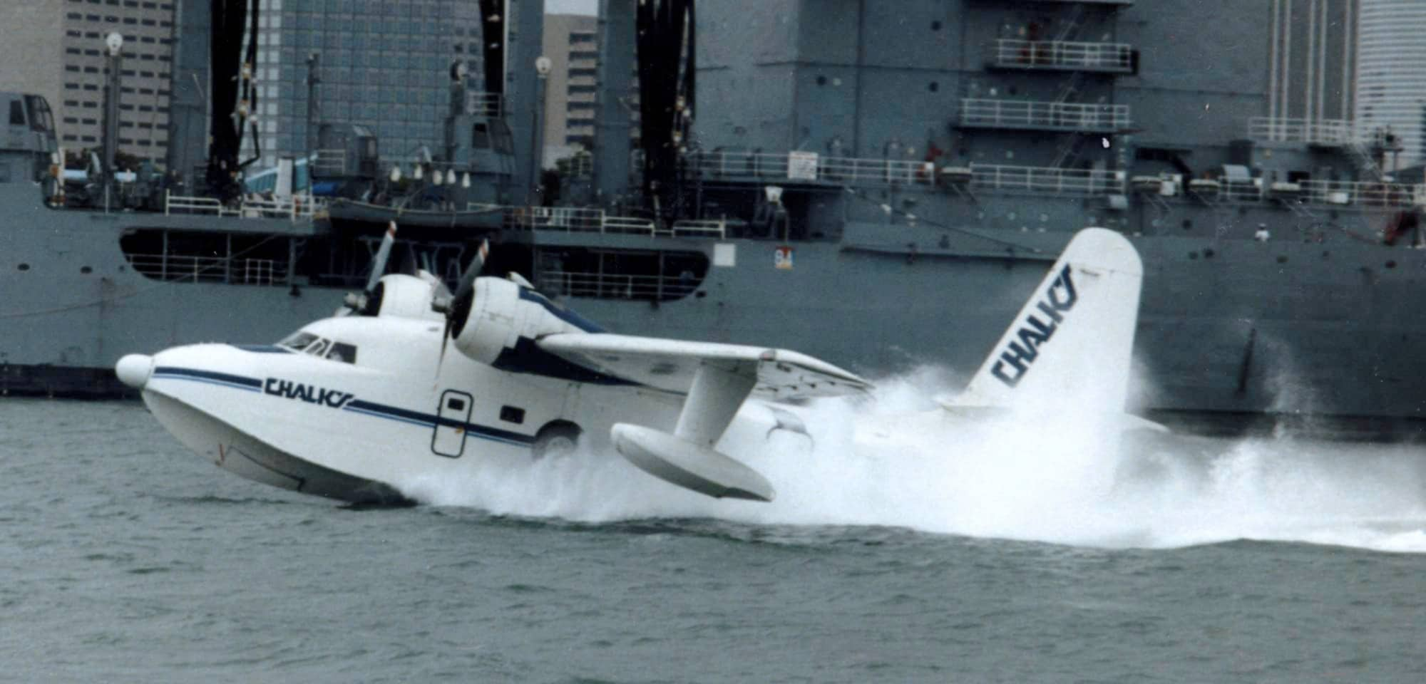 A seaplane landing in the harbor next to a battle ship